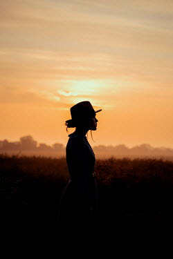 Rekha Garton SILHOUETTED WOMAN IN HAT IN COUNTRYSIDE WITH SUNSET Women