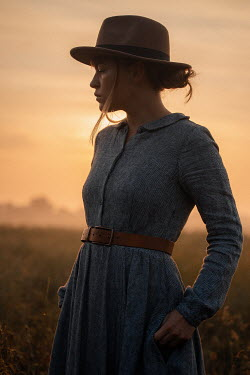 Rekha Garton WOMAN WITH HAT STANDING IN COUNTRYSIDE WITH SUNSET Women