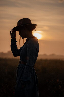 Rekha Garton WOMAN IN HAT IN COUNTRYSIDE WITH SUNSET Women