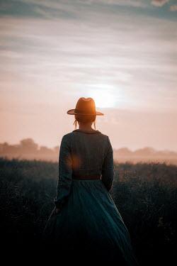 Rekha Garton WOMAN IN HAT WATCHING SUNSET IN COUNTRYSIDE Women