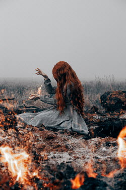 Rekha Garton WOMAN WITH RED HAIR SITTING IN BURNING FIELD Women