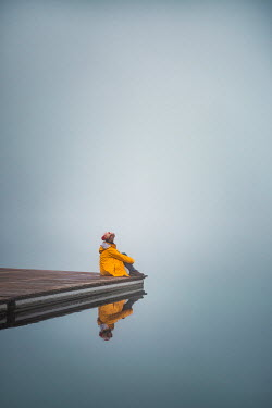 Evelina Kremsdorf WOMAN IN RAINCOAT SITTING ON JETTY BY LAKE Women