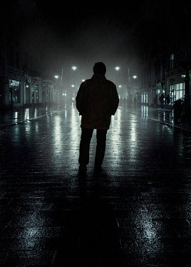 Jaroslaw Blaminsky SILHOUETTED MAN WALKING IN CITY STREET AT NIGHT Men