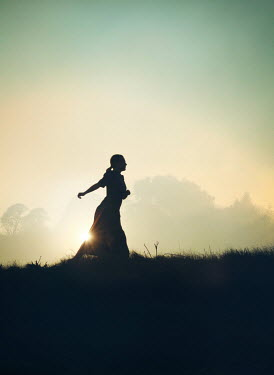 Mark Owen SILHOUETTED WOMAN RUNNING IN COUNTRYSIDE AT SUNSET Women
