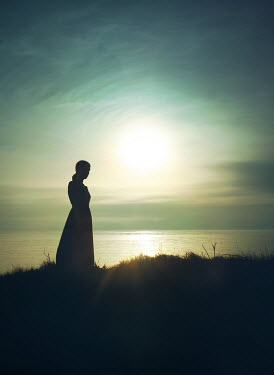 Mark Owen silhouetted woman watching sea at sunset Women