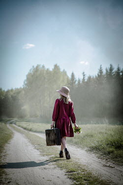Natasza Fiedotjew Vintage girl with suitcase walking away in coutryside