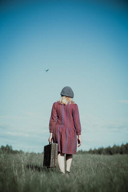 Natasza Fiedotjew Vintage girl with suitcase walking away in field