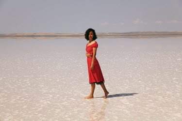 Esmahan Ozkan WOMAN IN RED DRESS WALKING ON BEACH Women