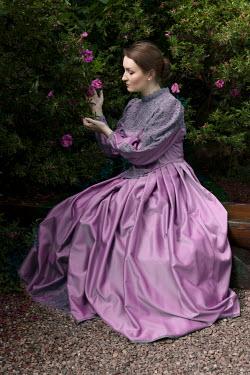 Jaroslaw Blaminsky HISTORICAL WOMAN IN PINK DRESS SITTING IN GARDEN Women