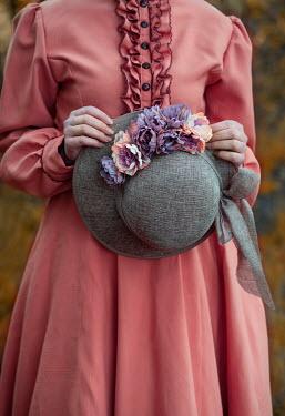 Jaroslaw Blaminsky WOMAN HOLDING HAT WITH FLOWERS OUTDOORS Women