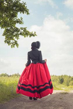 Joanna Czogala WOMAN IN BONNET WALKING ON COUNTRY PATH Women
