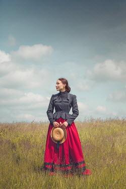 Joanna Czogala WOMAN HOLDING STRAW HAT IN SUMMERY FIELD Women