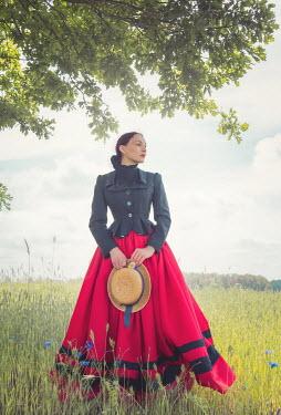 Joanna Czogala WOMAN CARRYING HAT IN SUMMERY COUNTRYSIDE Women