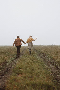 Shelley Richmond RUNNING COUPLE HOLDING HANDS IN FIELD Couples