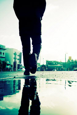 Tim Robinson SILHOUETTED MAN WALKING IN PUDDLE IN CITY Men