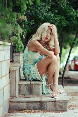 Irene Lamprakou BLONDE WOMAN IN SUMMER DRESS SITTING OUTDOORS Women