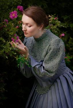 Jaroslaw Blaminsky WOMAN IN LACE GOWN SMELLING PINK FLOWERS OUTDOORS Women