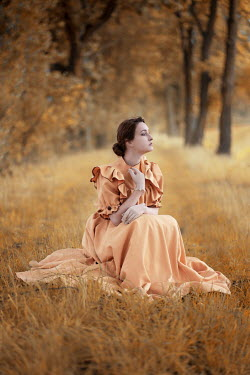 Jaroslaw Blaminsky WOMAN IN ORANGE GOWN SITTING IN AUTUMN COUNTRYSIDE Women