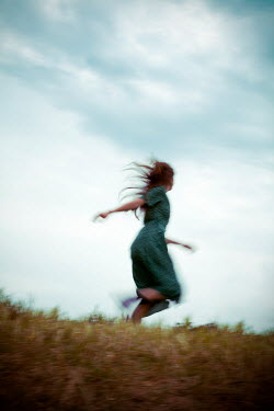 Miguel Sobreira Blurred Figure of Retro Woman Running on Grass