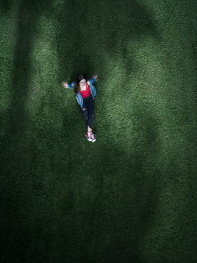 Magdalena Russocka teenage girl sitting on field from above