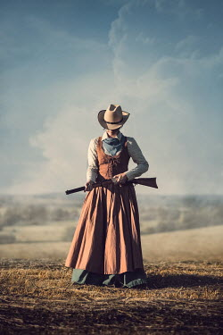 Magdalena Russocka historical woman in cowboy hat with rifle standing in countryside