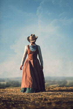Magdalena Russocka historical woman in cowboy hat with rifle walking in countryside