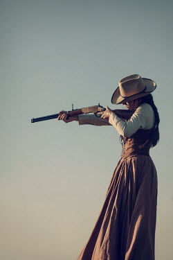 Magdalena Russocka historical woman in cowboy hat aiming with rifle in countryside