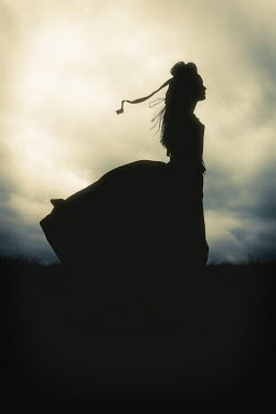 Shelley Richmond SILHOUETTED WOMAN IN WINDY COUNTRYSIDE AT DUSK Women
