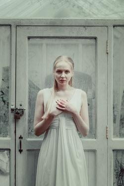 Nic Skerten BLONDE GIRL STANDING BY GLASS SUMMER HOUSE Women