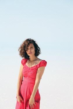 Esmahan Ozkan BRUNETTE WOMAN IN RED DRESS ON BEACH Women