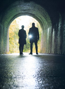 Mark Owen SILHOUETTED COUPLE STANDING IN TUNNEL WITH TORCH Couples