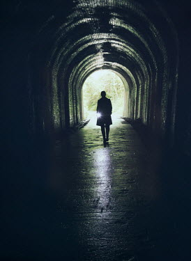 Mark Owen SILHOUETTED WOMAN WITH TORCH IN TUNNEL Women