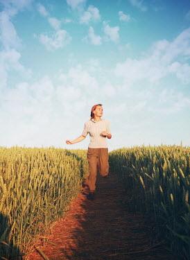Mark Owen BLONDE WOMAN RUNNING IN WHEAT FIELD Women