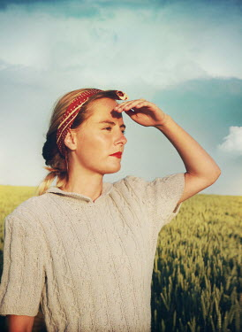 Mark Owen WOMAN SHIELDING EYES FROM SUN IN FIELD Women