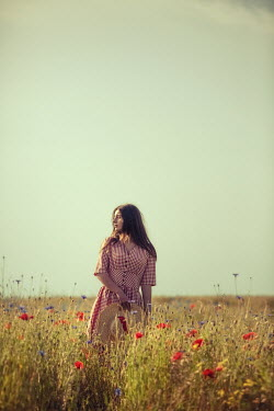 Magdalena Russocka young woman standing in poppy field