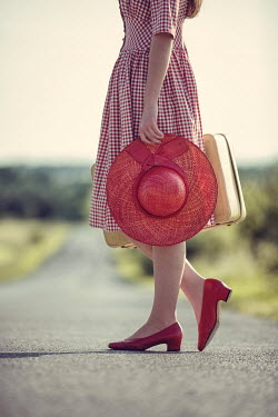Magdalena Russocka young woman with suitcase standing on country road