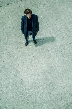 CollaborationJS MAN IN COAT STANDING ON CONCRETE FROM ABOVE Men