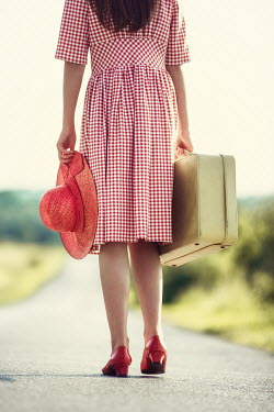 Magdalena Russocka young woman with suitcase walking on country road