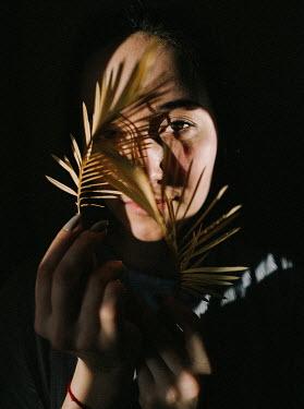 Daniil Kontorovich WOMAN HOLDING LEAVES OVER FACE IN SHADOW Women