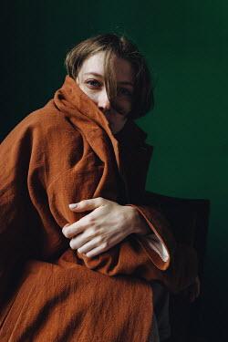Daniil Kontorovich BRUNETTE WOMAN SITTING IN COAT INDOORS Women