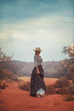 Ildiko Neer Historical woman in cowboy hat standing countryside