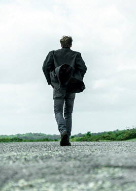CollaborationJS MAN IN RAINCOAT WALKING IN WINDY COUNTRYSIDE Men