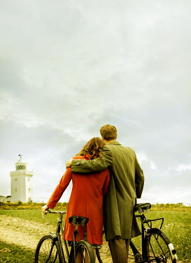 CollaborationJS RETRO COUPLE WITH BICYCLES HUGGING BY LIGHTHOUSE Couples