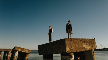 Daniil Kontorovich TWO MEN STANDING ON CONCRETE BLOCKS IN SEA Men