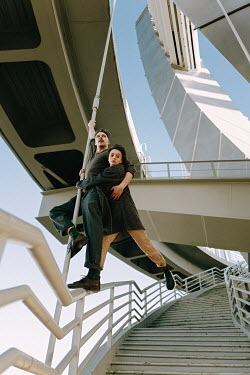 Daniil Kontorovich COUPLE BALANCING ON STEPS ON MODERN BUILDING Couples
