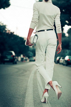 Irene Lamprakou WOMAN IN WHITE WITH STILETTOS STANDING IN STREET Women