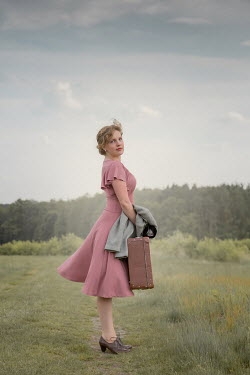 Joanna Czogala BLONDE WOMAN CARRYING SUITCASE IN COUNTRYSIDE Women