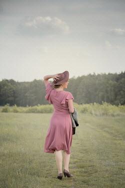 Joanna Czogala WOMAN IN HAT CARRYING WALKING IN COUNTRYSIDE Women