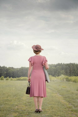Joanna Czogala WOMAN IN HAT STANDING IN COUNTRYSIDE Women