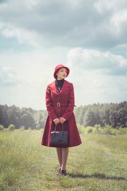 Joanna Czogala WOMAN IN RED HAT STANDING IN COUNTRYSIDE Women